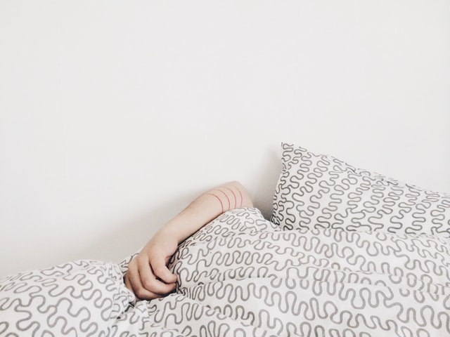 Person sleeping under covers.