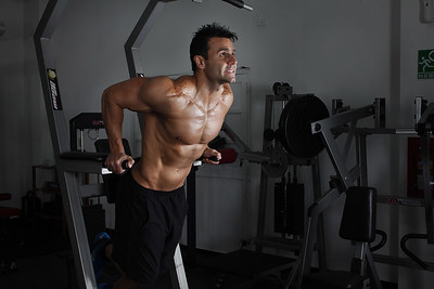 Man using a dip bar and doing dips to exercise.