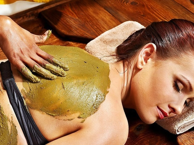 Woman getting cream rubbed onto her back.