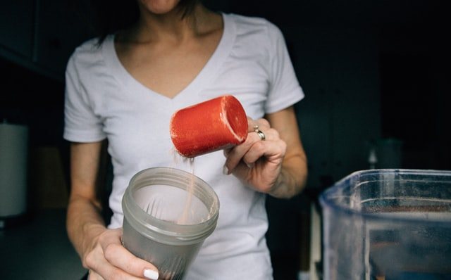 Woman pouring protein powder into cup.