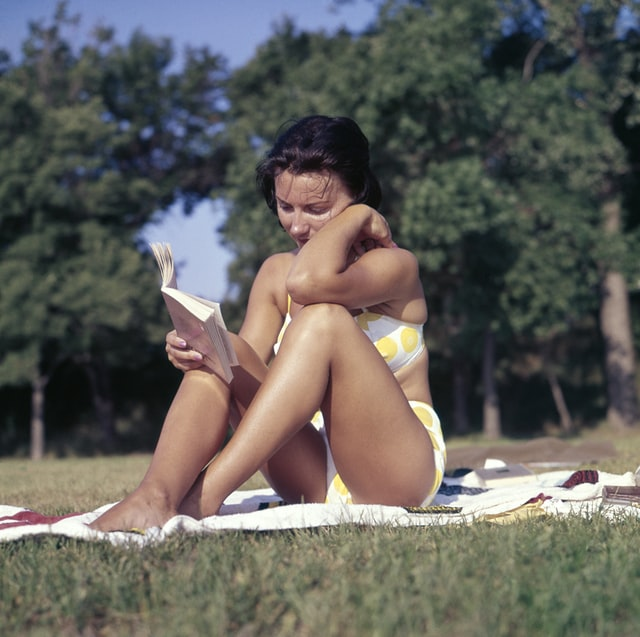 Woman sitting on the ground reading a book.
