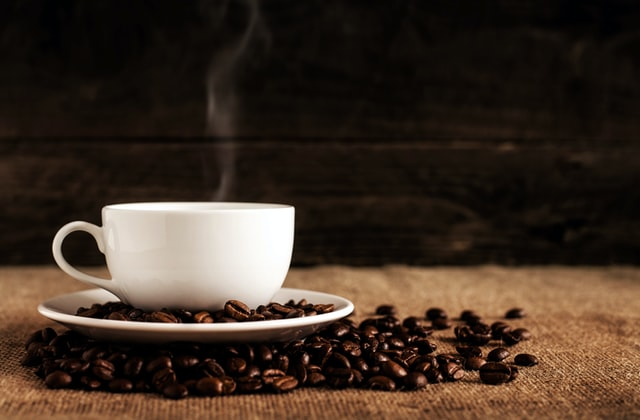 A cup of coffee with coffee beans around it.