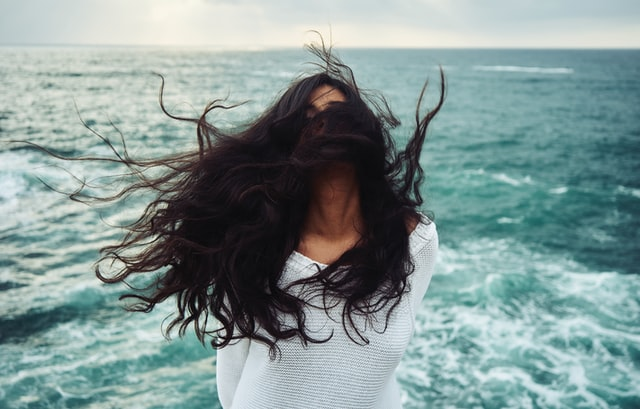 Woman with her hair in front of her face.