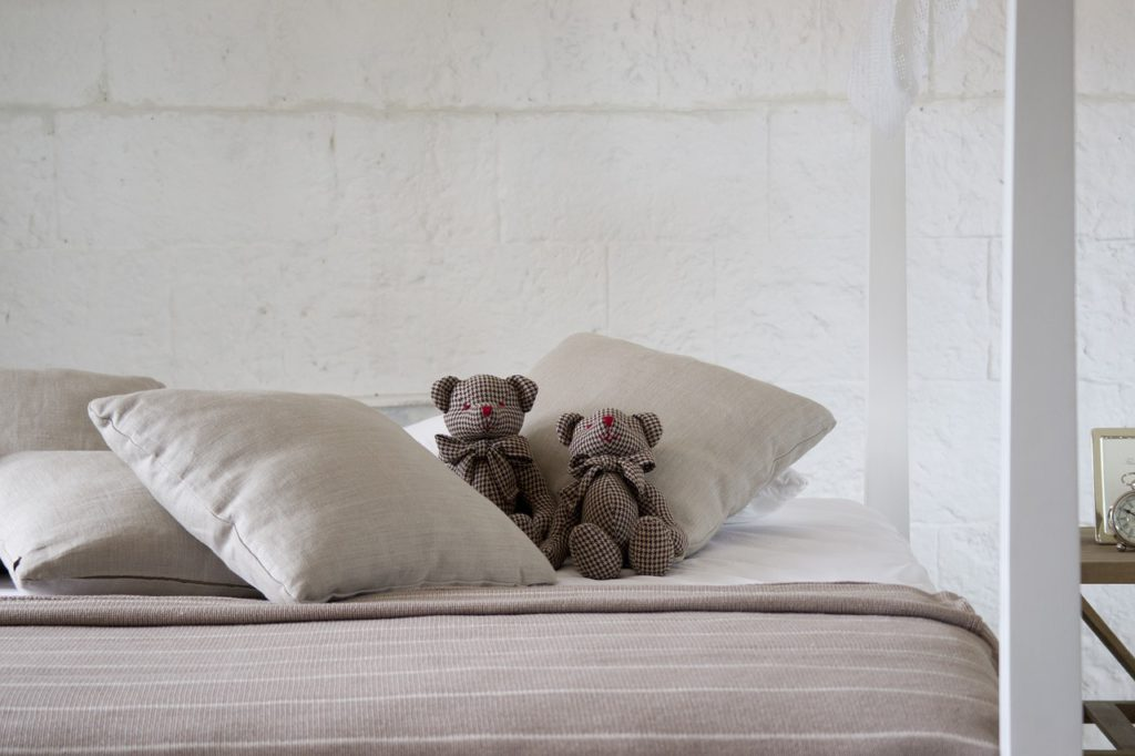 Bed with teddy bears for rest.