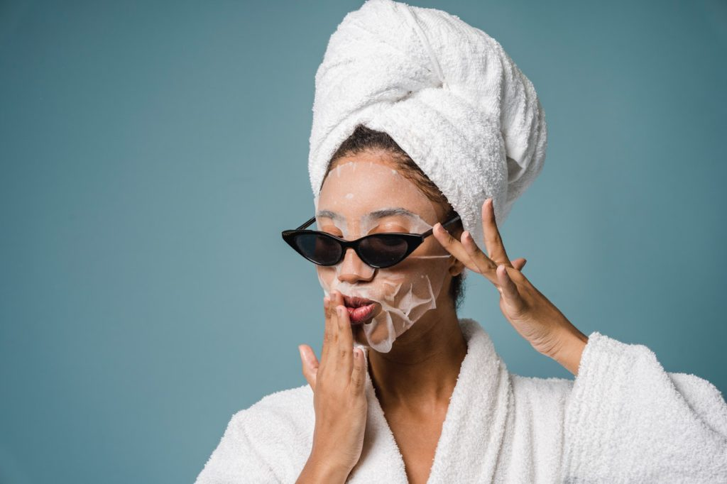 Woman using a face mask to treat her skin.