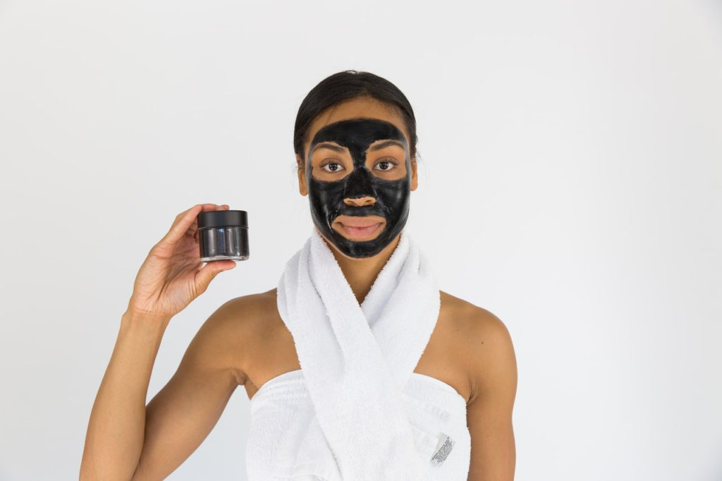 Woman using facial cleanser for skincare.
