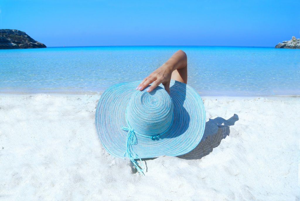 woman with blue hat on white sandy beach outlooking blue ocean