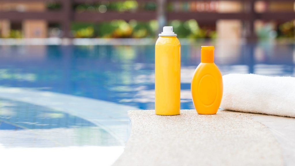 two yellow bottles of sunscreen sit beside pool