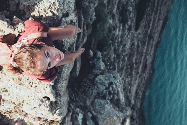 Woman sitting on a cliff edge looking up.