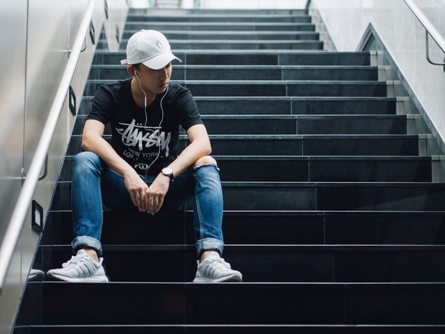 Man sitting on stairs listening to music.