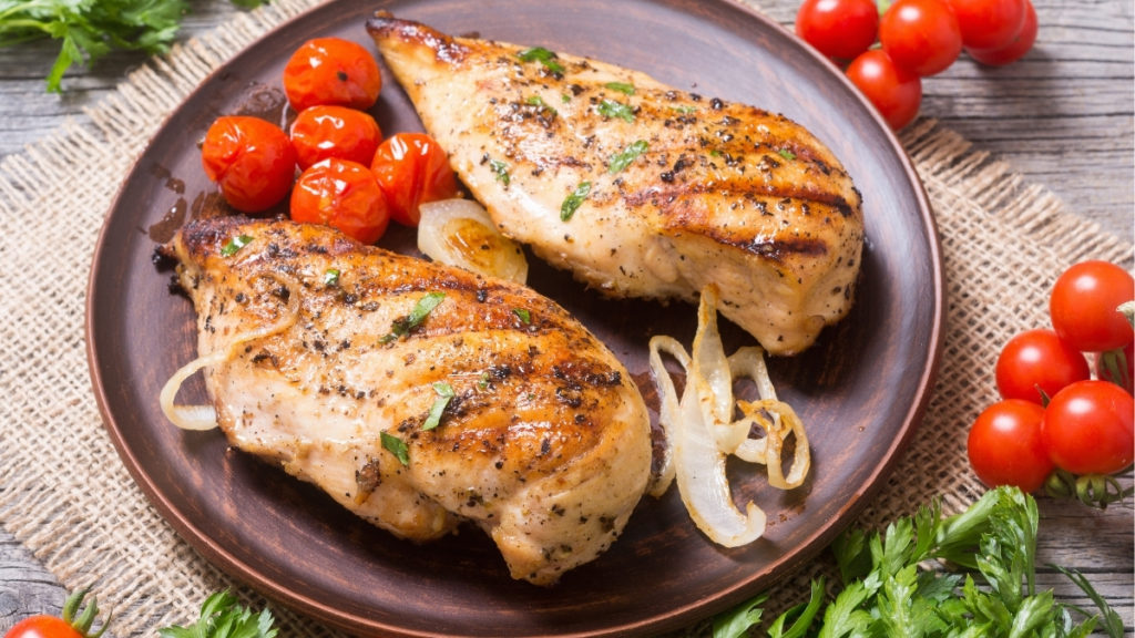 chicken breast on plate with cherry tomatoes and white onions