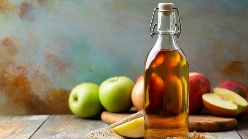 apple cider vinegar bottled with red and green apples in background