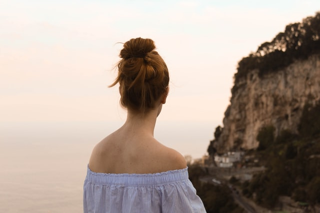 Woman outside by a cliff.