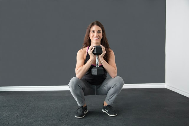 Woman squatting with a dumbbell.