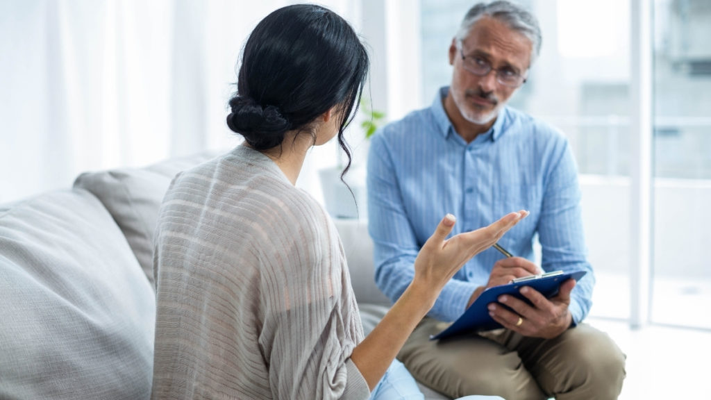 woman sitting with therapist in person