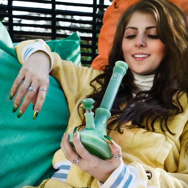 Woman with a bong laying down.