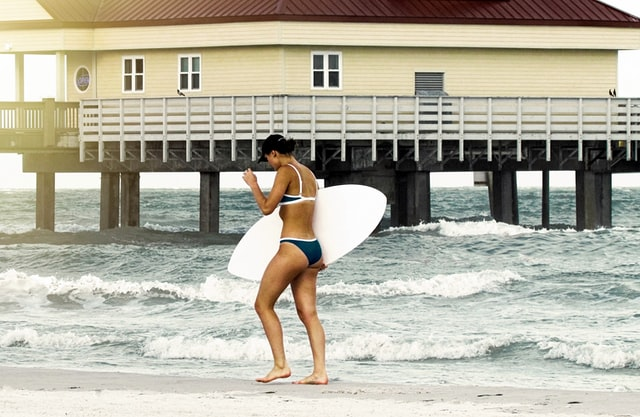 A woman on a beach with a surf board.