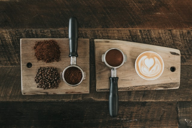 Various coffee beans and grounds with a mug full of coffee on a table.