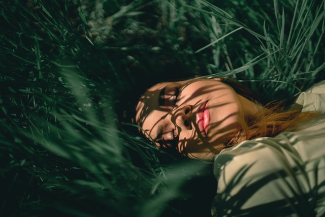 Woman with clear skin laying in the grass.