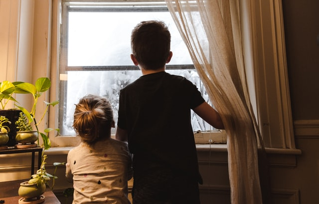 Two kids looking out a window.