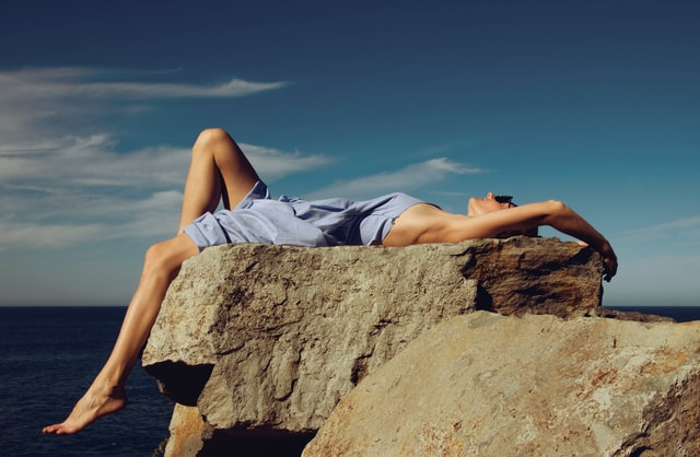 A woman laying down on a rock.