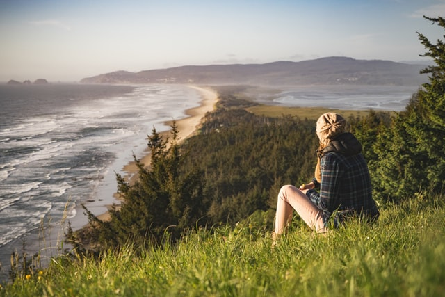 A woman sitting on a hill looking at a body of water.