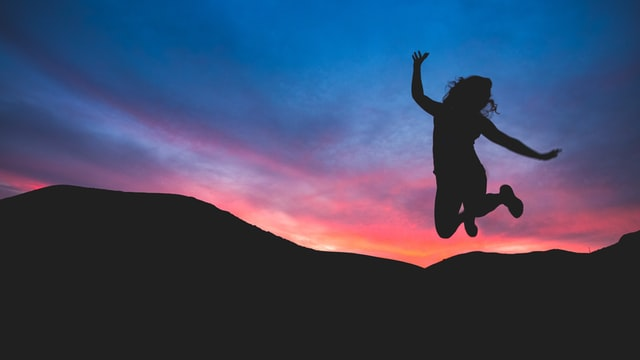 A woman jumping in the air at sunset.