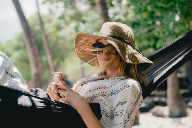 A woman relaxing on a hammock with her phone.